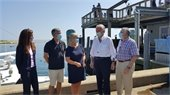 Town officials and Senator Markey standing on at the Fish Pier in front of the water.