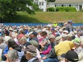 Town Meeting attendees sitting on Veterans Field