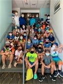 Masked kids sitting in a stairwell at the Community Center.