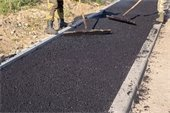 Two men smoothing black asphalt to construct a sidewalk
